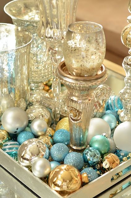 a tray with silver, pearl and turquouise glitter ornaments and candles for coastal decor
