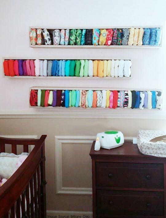 box shelves with different colorful diapers over the changing table