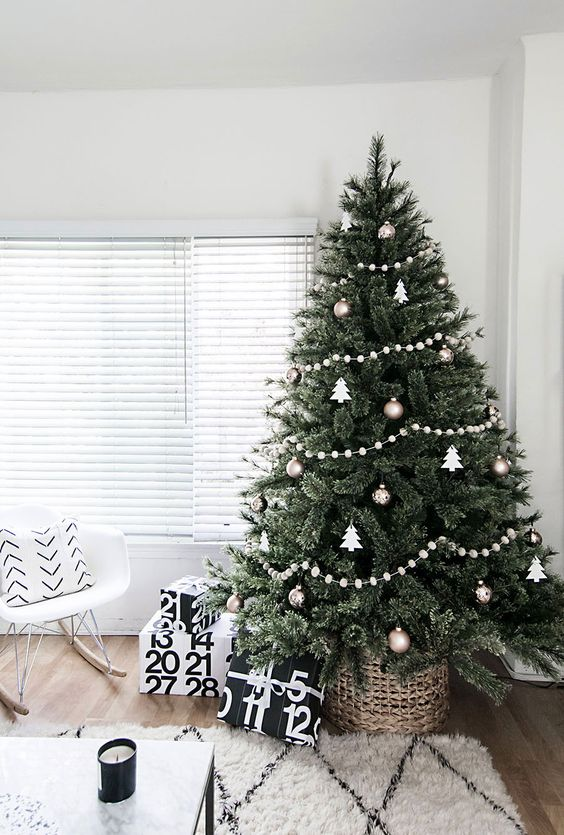 a Christmas tree with metallic and white ornaments and white felt ball garlands