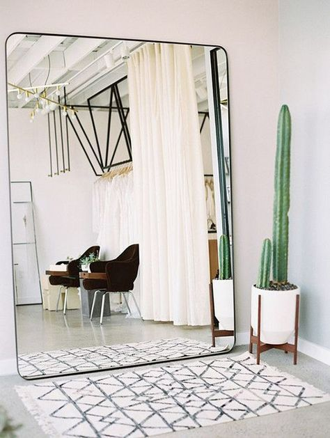 a Scandinavian entryway with a large mirror in a black frame that visually doubles the space