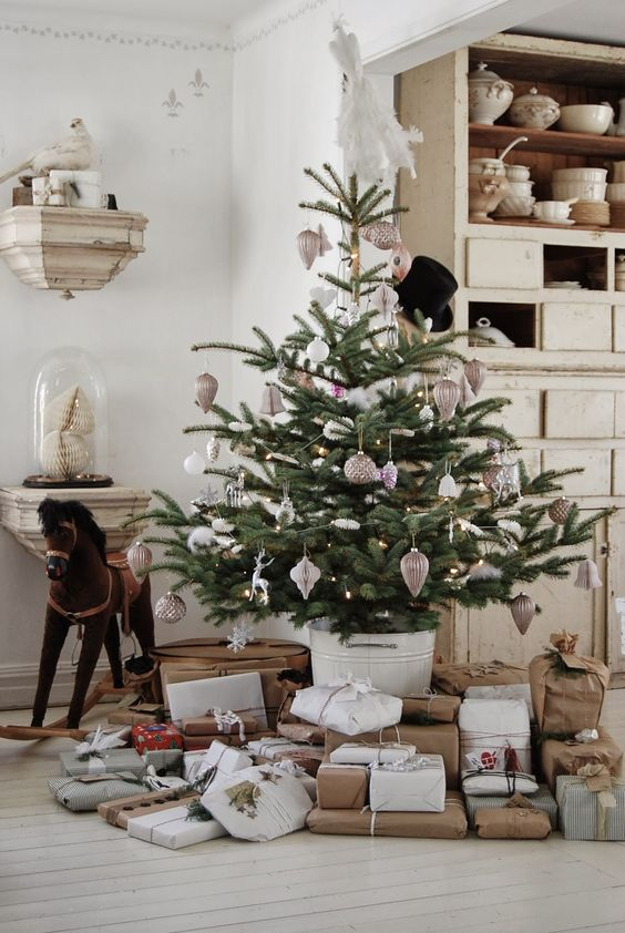 a Christmas tree with vintage white and copper ornaments and paper garlands