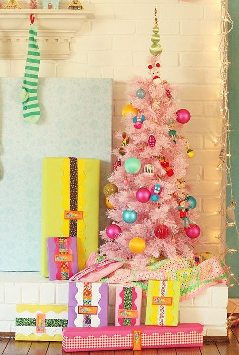 a cute pastel pink Christmas tree with colorful ornaments for a child's space