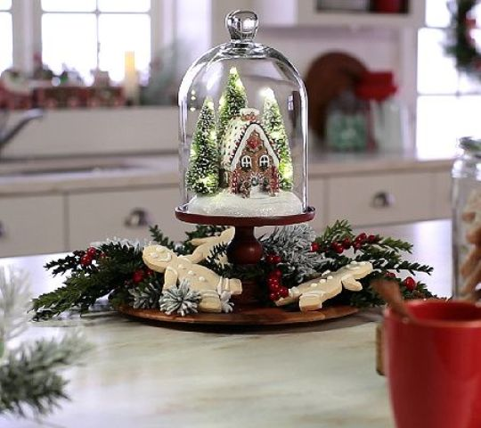 a small winter terrarium with a faux gingerbread house and Christmas trees