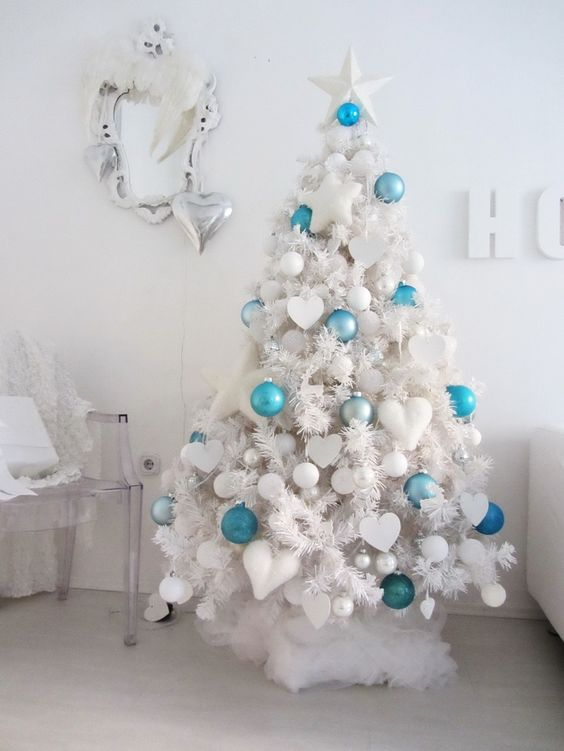 a white tree with white ornaments and some bold turquoise and blue ones to make it stand out