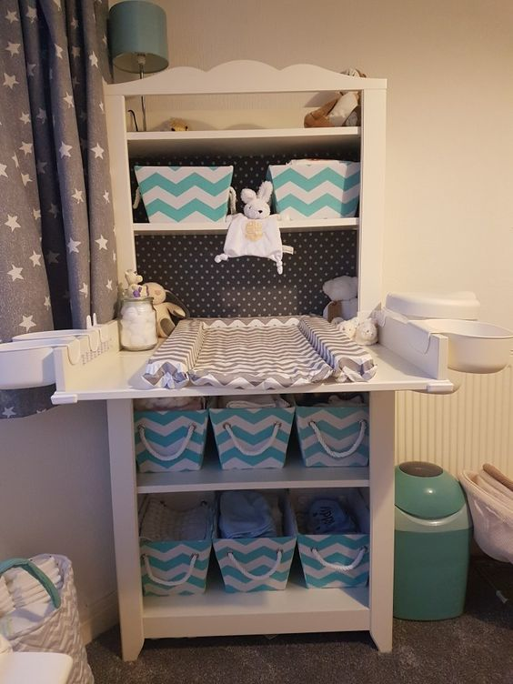 a comfy changing table with fabric crates to store diapers and other things