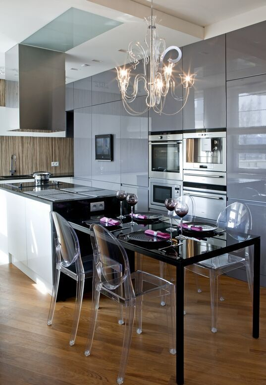 a modern kitchen island with an additional dining table part of dark metal