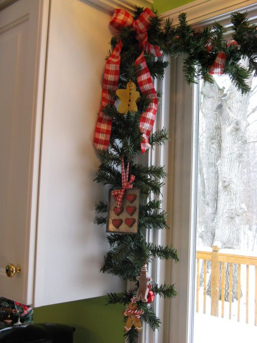 an evergreen garland with gingerbread inspired ornaments for decorating a window