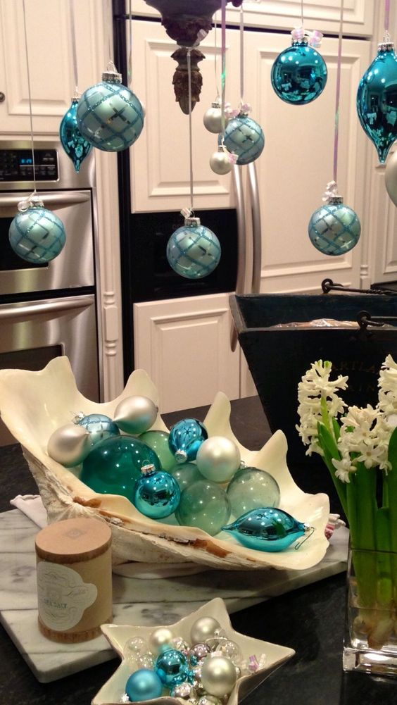 blue and turquoise ornaments hanging from the chandelier and a large shell with them and glass bubbles