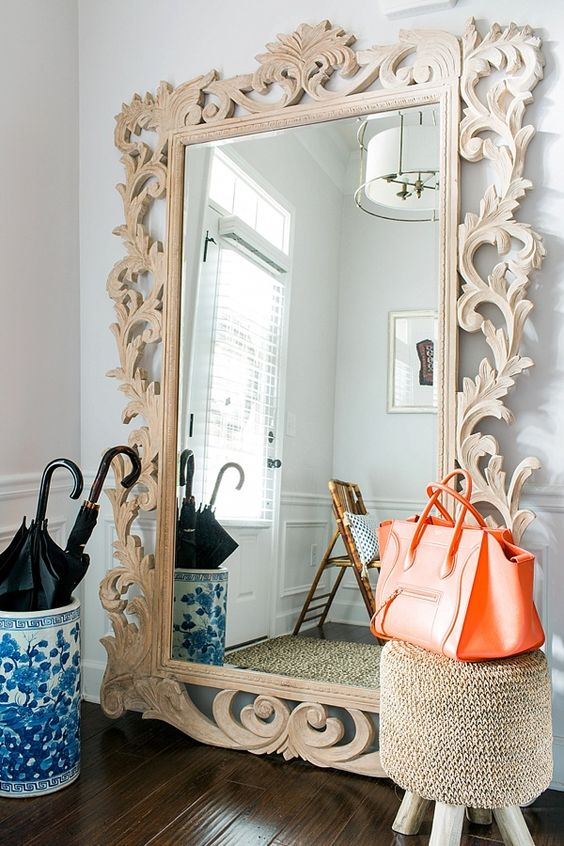 design a chic entryway with a mirror in a wood carved frame