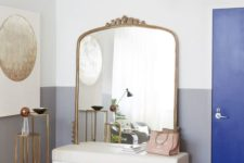 15 a glam entryway with a large mirror in a brass frame and soem other brass accents