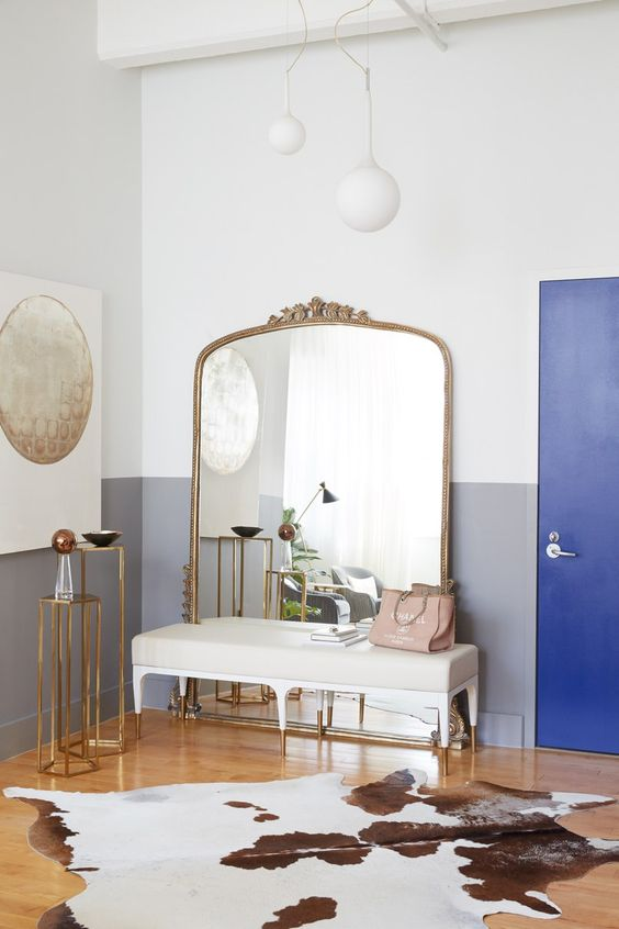 a glam entryway with a large mirror in a brass frame and soem other brass accents