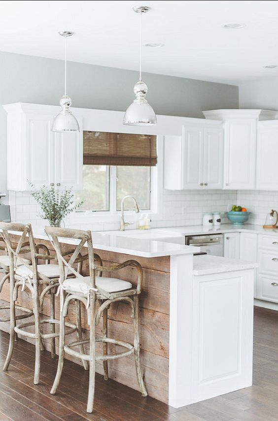 a rustic kitchen island with an elevated breakfast zone and rustic stools