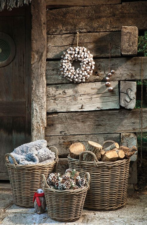 baskets with pinecones, firewood and blankets for decorating a winter porch