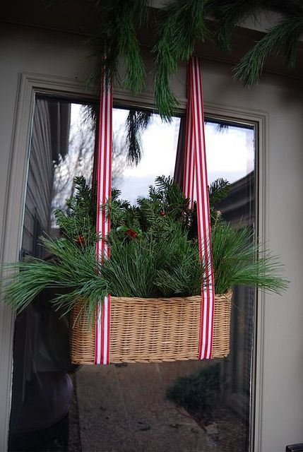 a hanging basket with striped ribbons, evergreens and berries for the front door