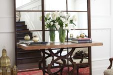 16 a large mirror with aged metal framing for an eclectic space