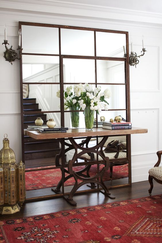 a large mirror with aged metal framing for an eclectic space