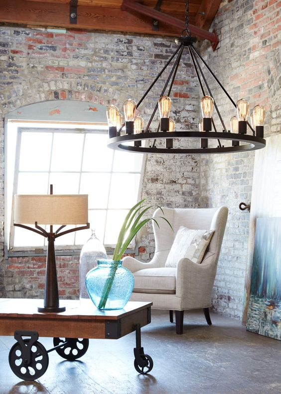 a wide round black chandelier with lots of bulbs will fit a rustic industrial space
