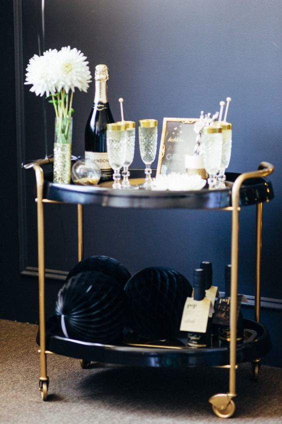 a black and gold cart with gold rim glasses and large pipe balls for an elegant feel