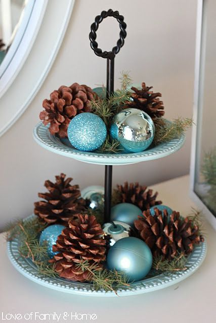 a blue porcelain cupcake stand with silver and turquoise ornaments, evergreens and pinecones