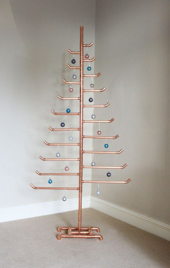 a copper pipe Christmas tree with various colorful ornaments