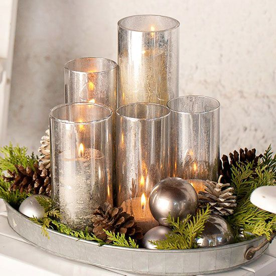 a rustic tray with evergreens, pinecones, silver ornaments and mercury glass candle holders