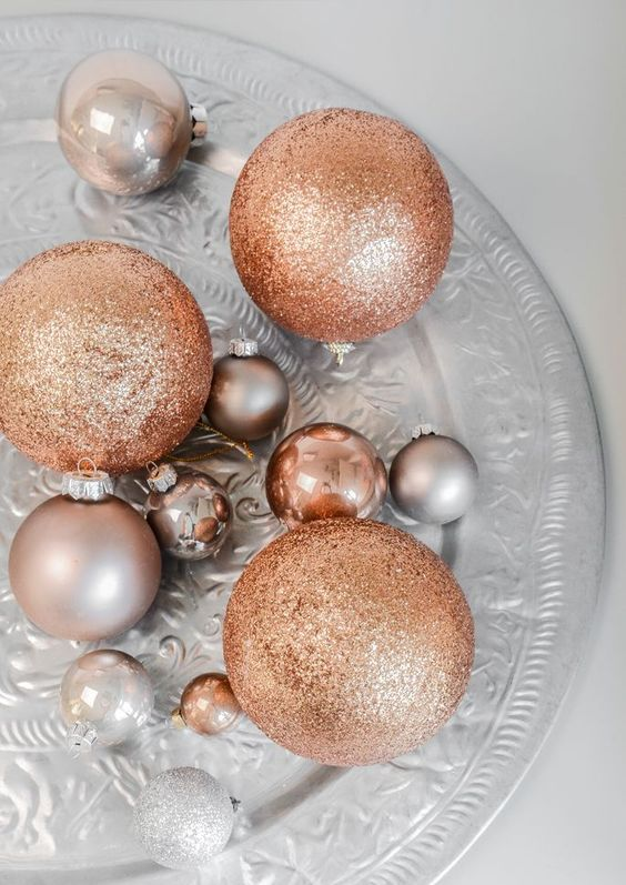 an arrangements of silver and copper glitter ornaments for festive decor