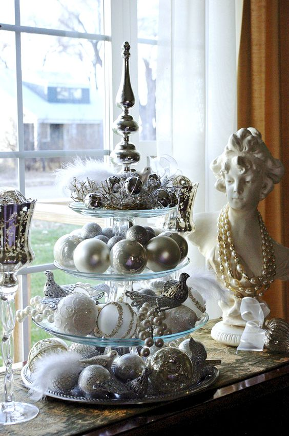 a glass cupcake stand with silver and pearly ornaments and beaded garlands