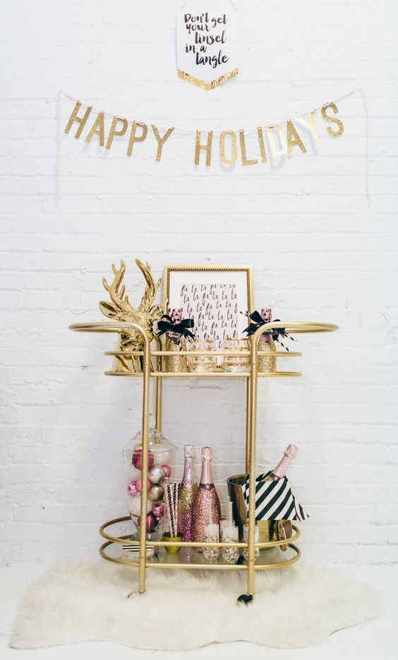 a gold deer head, a tall jar with colorful ornaments and glitter champagne bottles