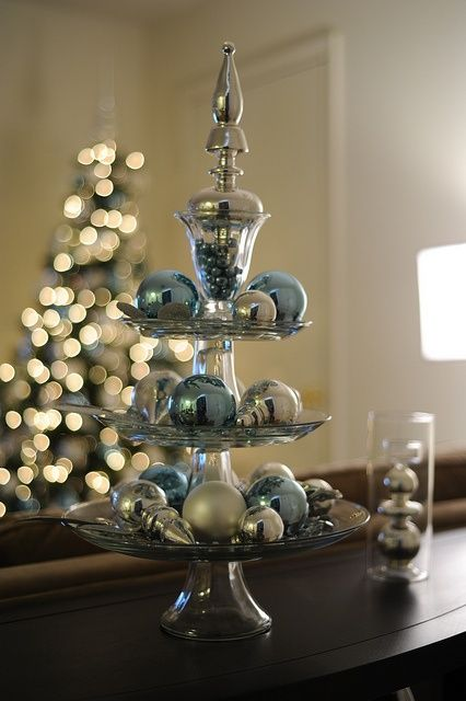 a glass stand with silver and blue shiny ornaments for a glam look