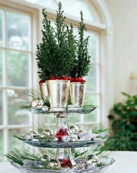 a glass stand with silver ornaments and silver julep cups