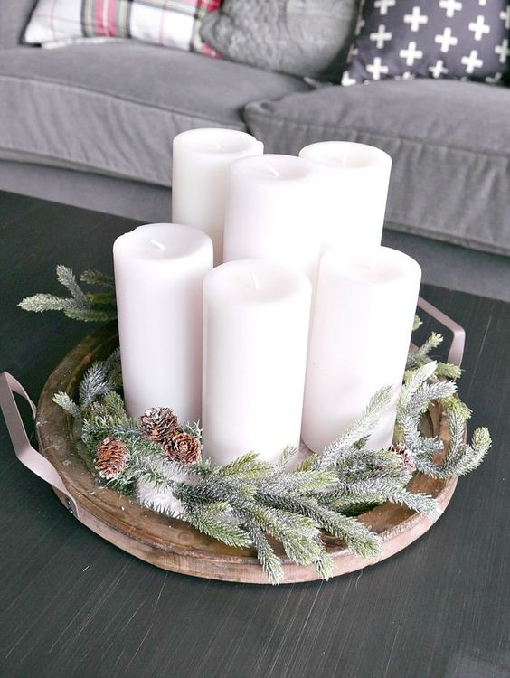 a wooden tray with evergreens, pinecones and candles is a simple and cozy display to make