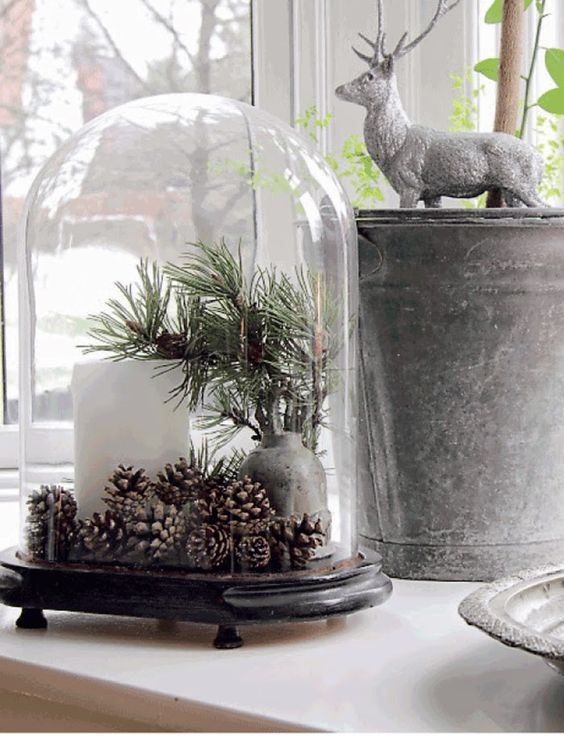 a large cloche with a pillar candle, pinecones and pine branches in a vase