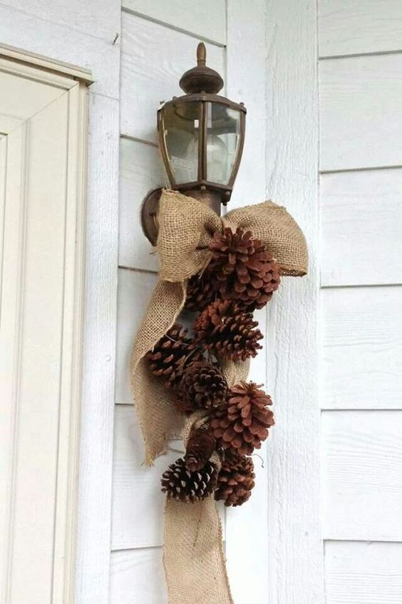 a burlap posie with pinecones for decorating the outdoor space