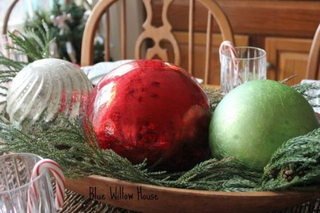 a holiday centerpiece of a dough bowl, evergreens and large Christmas ornaments