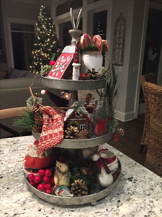 a metal cupcake stand with pinecones, berries, stockings, candy canes and gingerbread houses for a vintage feel