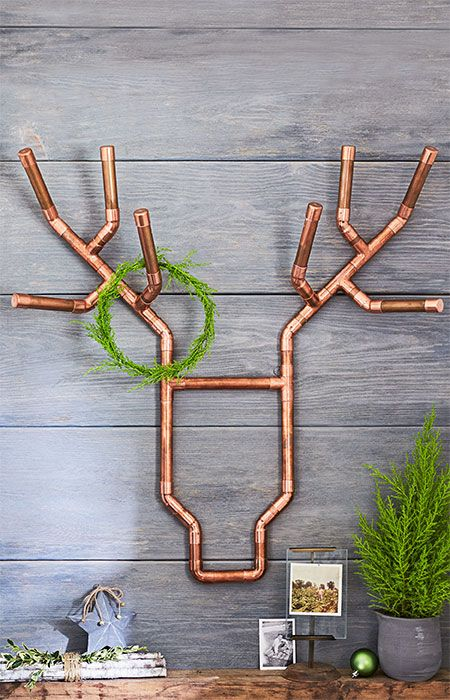 a creative deer head of copper pipes with a small green wreath for a modern space