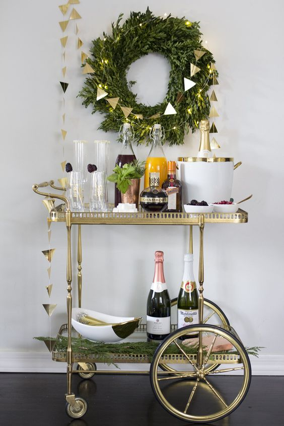 a gold rim bar cart with fresh greenery in a copper goblet, sugar rim glasses, berries and champagne