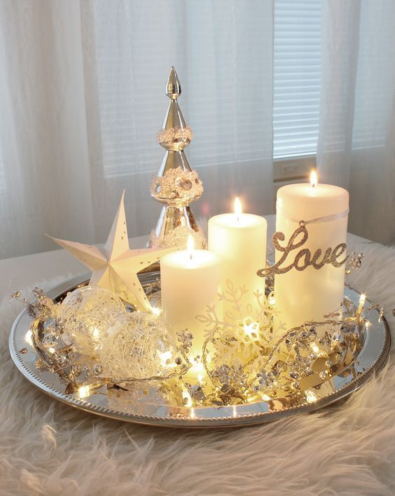 a silver round tray with LEDs, candles, glass ornaments and a silver Christmas tree for a glam touch