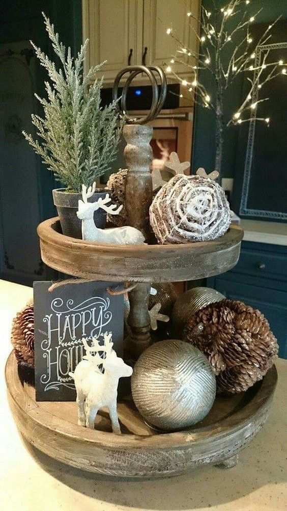 a wooden stand with evergreens, deer figurines, chalkboard signs and pinecones