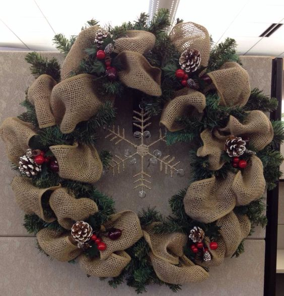 a rustic wreath of evergreens and burlap, snowy pinecones, berries and a gold snowflake