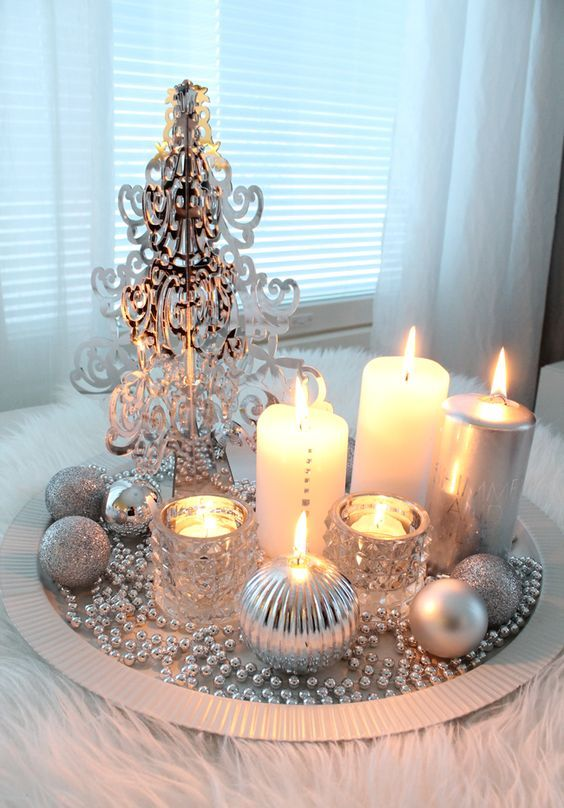 a silver tray with beads, a plastic tree, candles and silver ornaments for a glam space