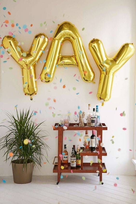 a step bar cart with large gold letter balloons over it - you won't need more decor