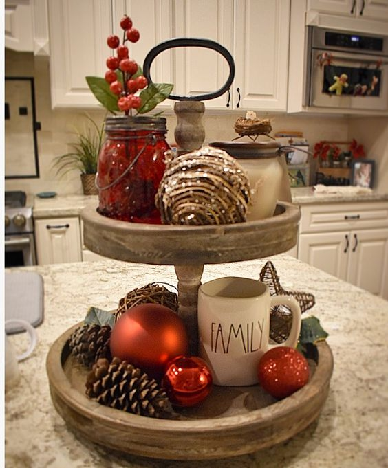 a two-tier tray with ornaments, pinecones, mason jars with berries and mugs