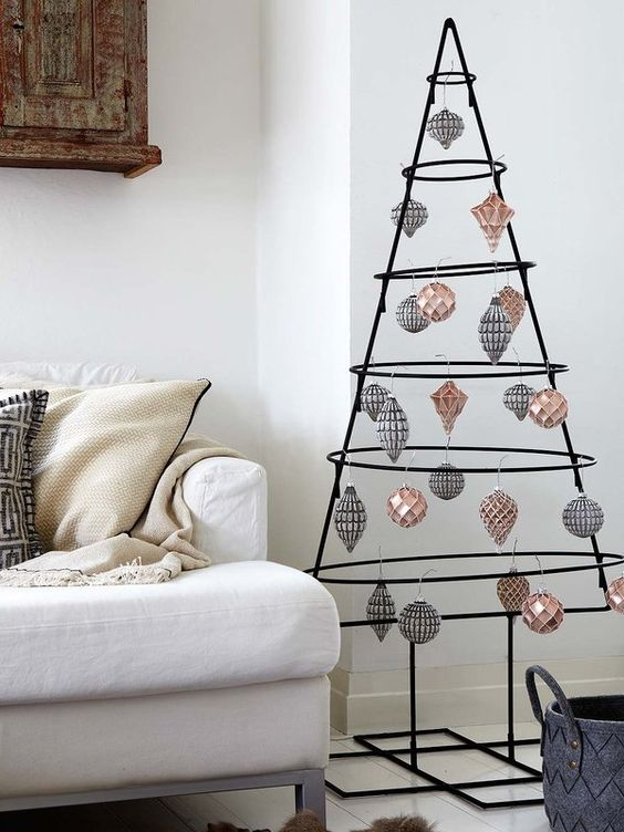 a wrought black Christmas tree with metallic ornaments of a graphic look