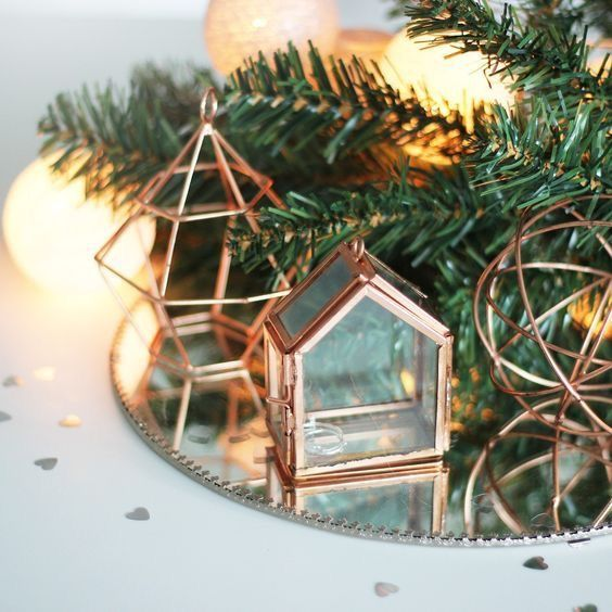 a mirror display with evergreens and copper terrariums and geometric figurines  for modern decor