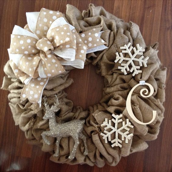 a burlap wreath with a ribbon bow, snowflakes, a monogram and a silver deer