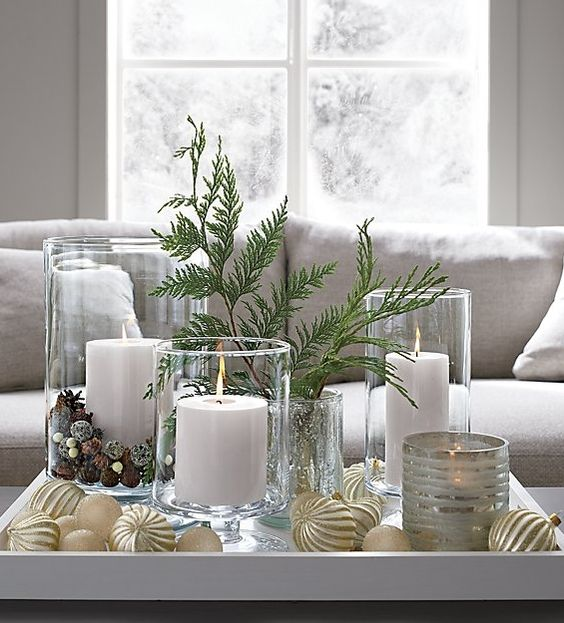 a tray with gold ornaments, evergreens, candles in glass candle holders and pinecones and beads