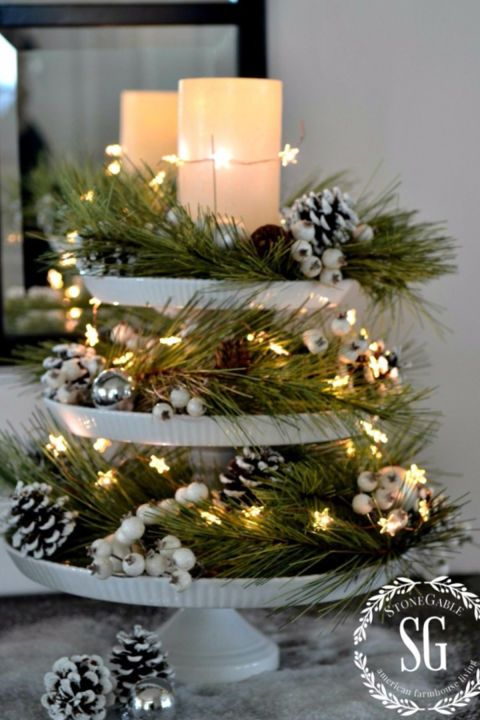 a white ceramic cupcake stand with candles, snowy pinecones, evergreens and twinkle star lights