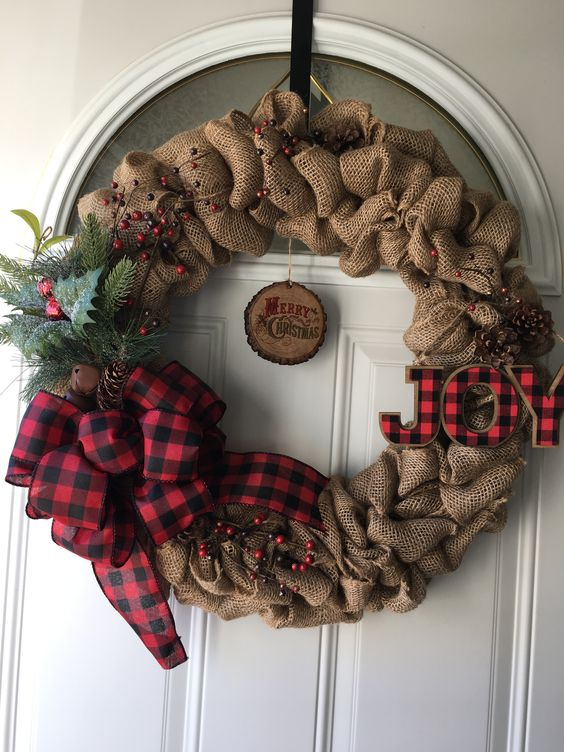 a burlap wreath with a plaid bow and letters, berries and faux greenery