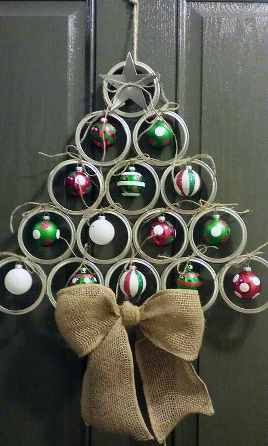 a wall-mount Christmas tree of metal with ornaments hanging inside and a burlap bow